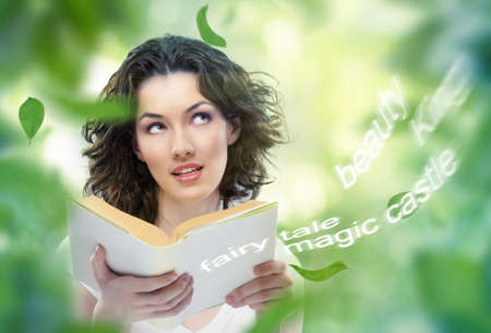 young beautiful girl reading a magic book photo
