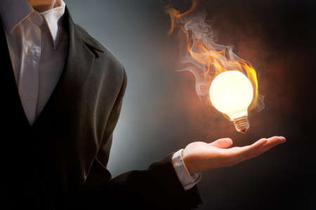 Business man holding fire light bulb