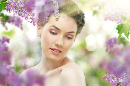 natural face: beautiful girl with a flower lilac