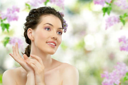 beauty care: beautiful girl with a flower lilac