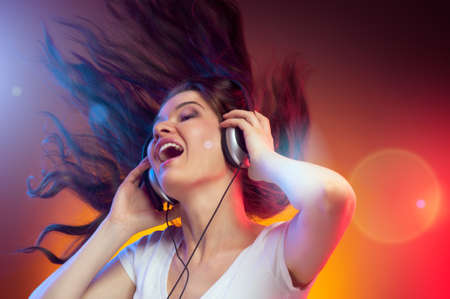 woman listening to music: girl with headphones in the club