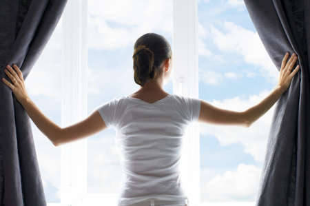 windows: girl opens the curtains Stock Photo