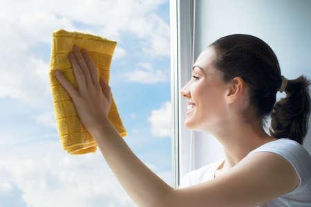 mujer limpiando: mujer joven lavando ventanas Foto de archivo