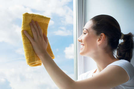 window cleaning: young woman washing windows