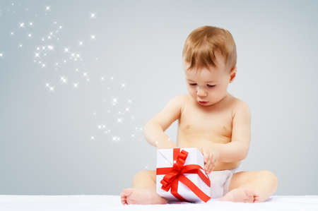 baby open present: beautiful child opens a gift Stock Photo