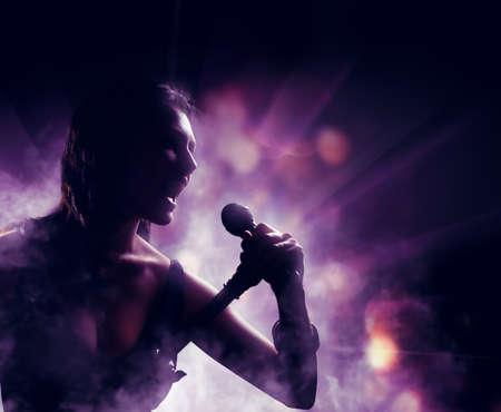 cantando: silueta de una mujer sobre un fondo de luces