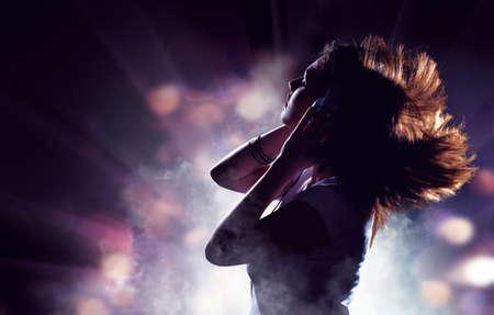 listening to music: silueta de una mujer sobre un fondo de luces
