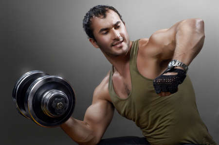 bicep: powerful muscular man lifting weights  Stock Photo