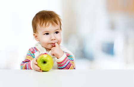 little child eating green apple photo