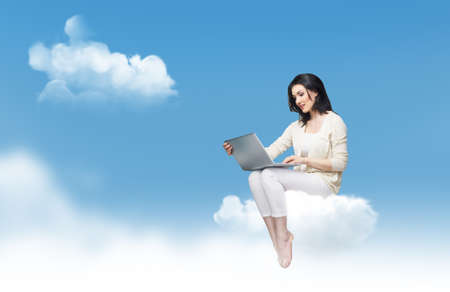cloud computer: Girl working on computer in sky Stock Photo