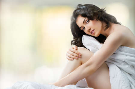 young nude girl: Mädchen sitzt auf dem Bett Lizenzfreie Bilder