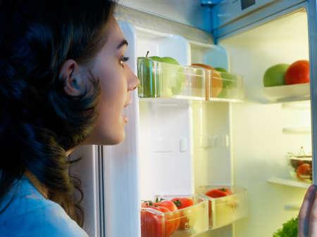 kühl: ein hungriges M�dchen �ffnet den K�hlschrank