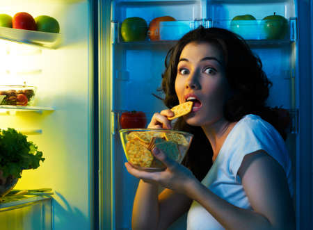 een hongerige meisje opent de koelkast