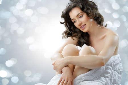 jeune femme nue: jeune fille assise sur le lit Banque d'images