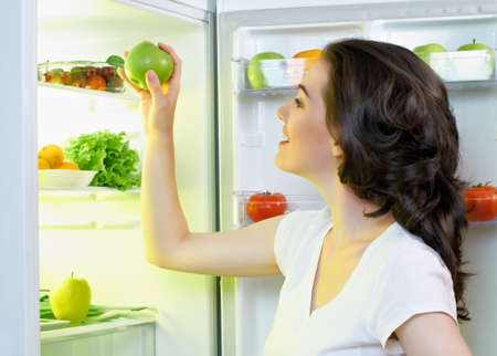 refrigerator with food: a hungry girl opens the fridge