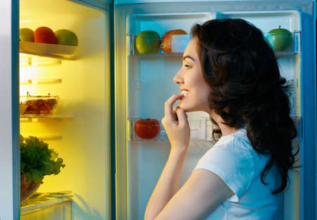 refrigerador: una niña de hambre abre la nevera Foto de archivo