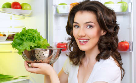 a hungry girl opens the fridge Stock Photo - 14420910