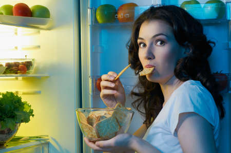 refrigerator: a hungry girl opens the fridge