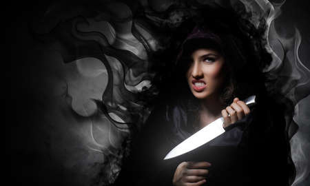 woman knife: Young beautiful witch. Halloween day