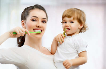 mother and daughter brush their teeth photo