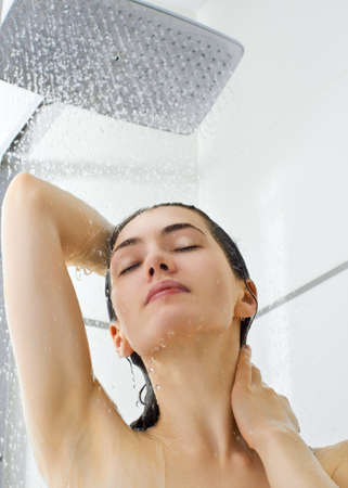 showering: a beautiful girl standing at the shower