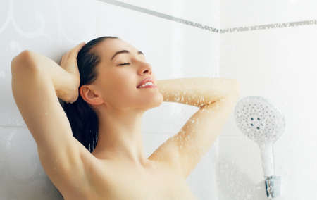 shower water: a beautiful girl standing at the shower