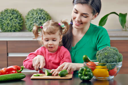 mother cooking: mother and daughter prepare salads