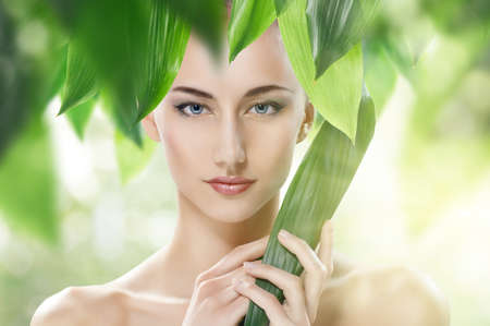 beautiful girl and green leaves photo