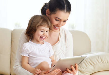 using computer: happy mother holding her child