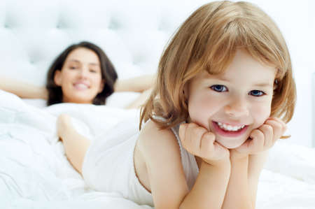 child in bed: daughter and mother are happy together