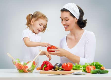 niños cocinando: madre e hija preparar ensaladas