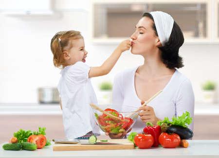 children cooking: madre e hija preparar ensaladas