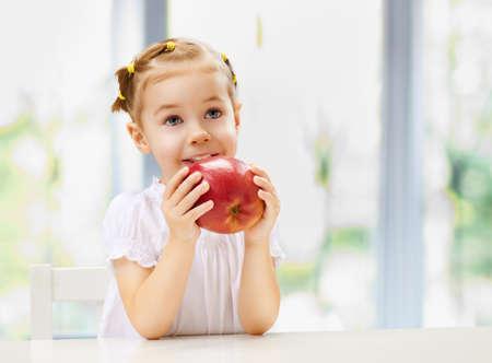 little girl eating: beauty girl holding red apple