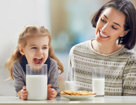 girl drinking milk at the kitchen photo
