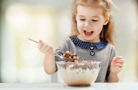 girl eating flakes at the kitchen photo