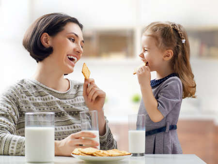 mom and child: girl and mother drinking milk and eat biscuits at the kitchen Stock Photo