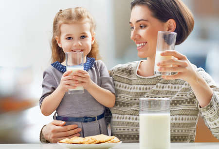 milk and cookies: girl drinking milk at the kitchen
