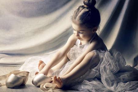 niños bailando: Niña que intenta en los zapatos de ballet