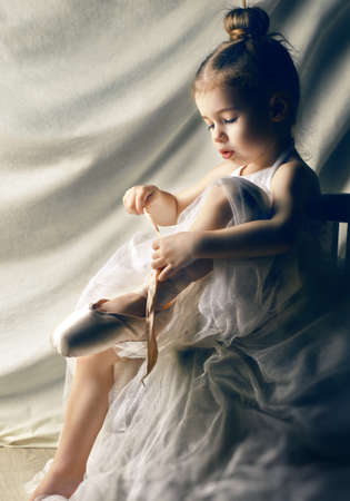Klein meisje probeert op balletschoenen Stockfoto