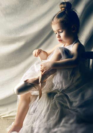 Petite fille essayant sur les chaussures de ballet Banque d'images - 26045851
