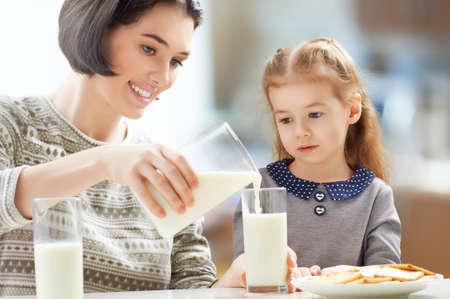 mother milk: girl drinking milk at the kitchen