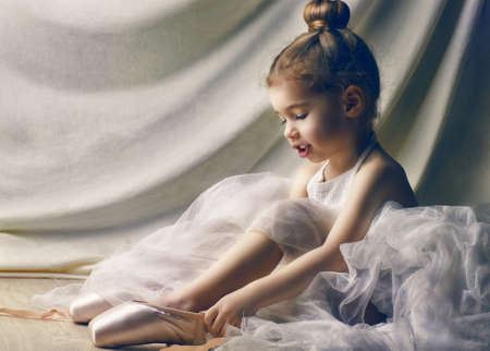 ballet clásico: Niña que intenta en los zapatos de ballet