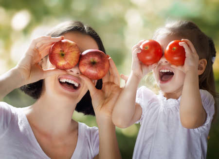 healthy girl: happy family keeps fresh vegetables Stock Photo