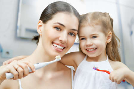 beautiful woman smiling: madre e hija se cepillan los dientes