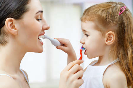 girl teeth: mother and daughter brush my teeth Stock Photo