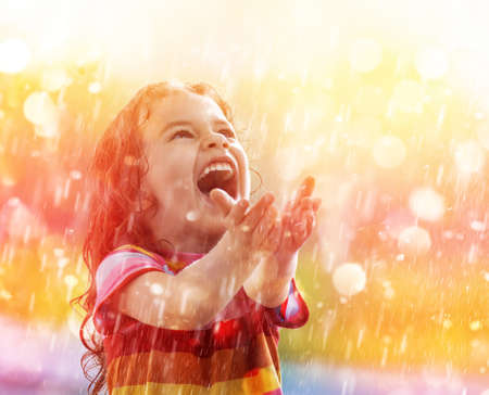 girl in rain: the child is happy with the rain Stock Photo