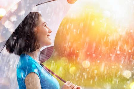 lluvia paraguas: una lluvia feliz mujer sonriente