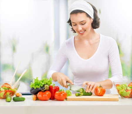 woman in kitchen making salad Stock Photo