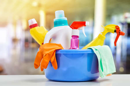 Basket with cleaning items on blurry background Stock Photo