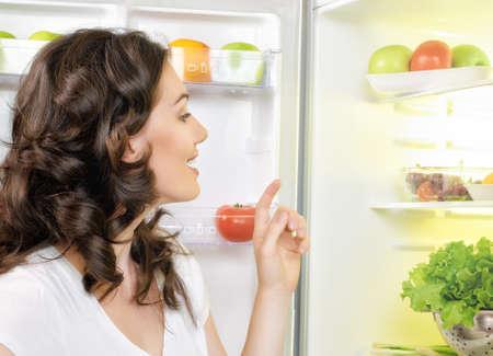 배고픈 소녀는 냉장고를 엽니 다